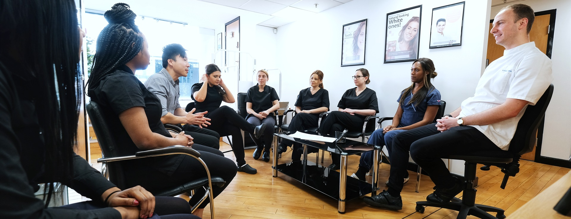 A group of dental professionals sitting in a semi circle mid-discussion.
